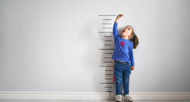 Little girl measuring herself against wall ruler