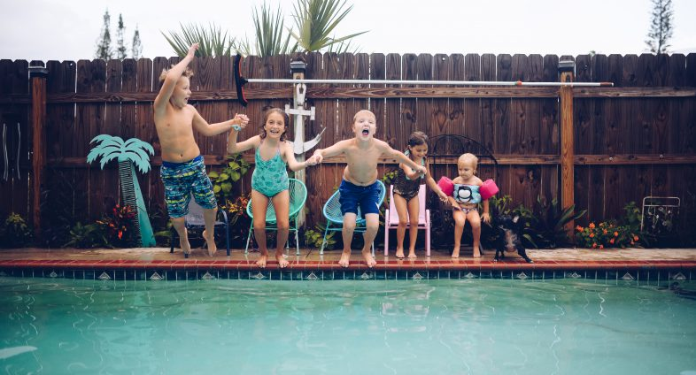 group of young kids jumping in backyard pool