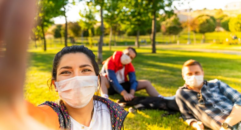 3 young adults outside wearing face masks and physically distancing